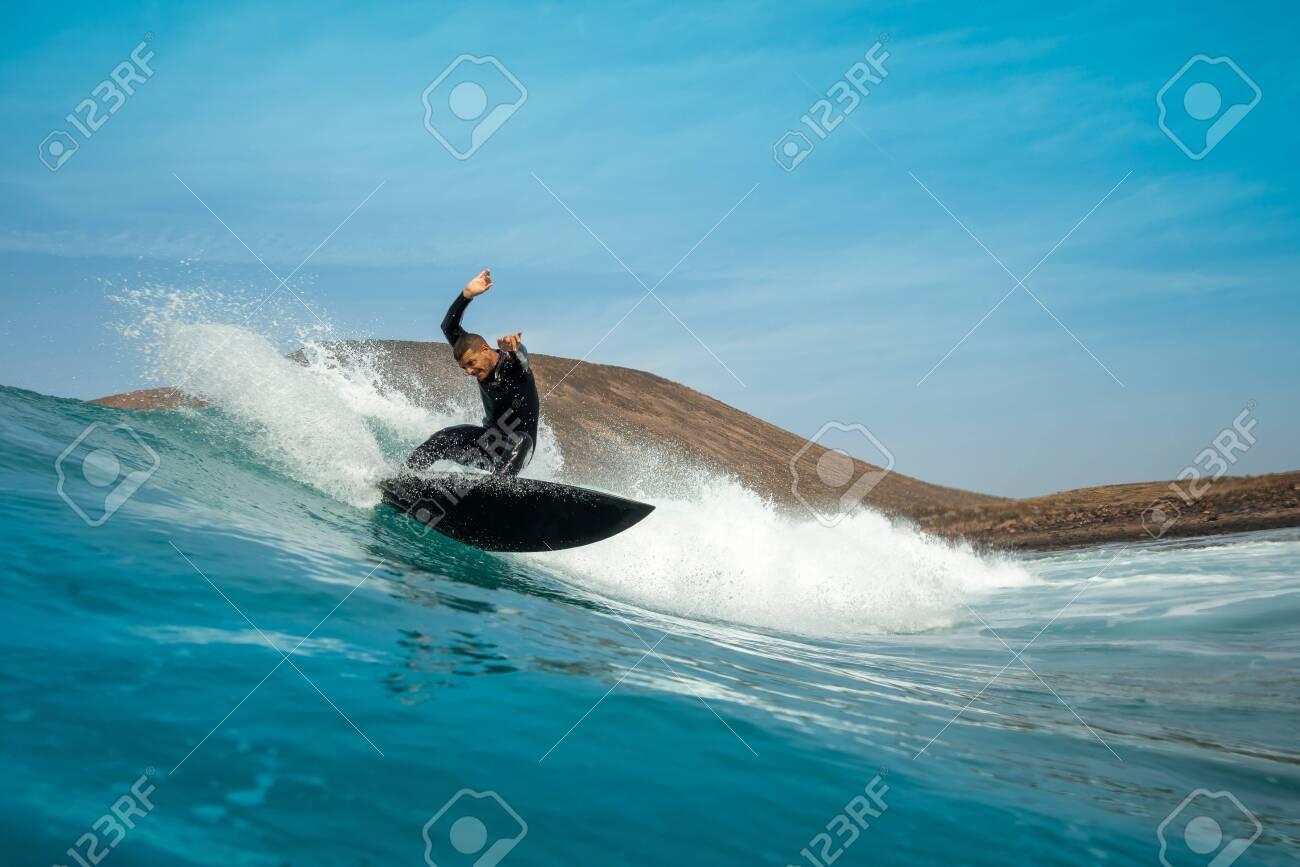 surfer riding waves on the island of fuerteventura - 143160044