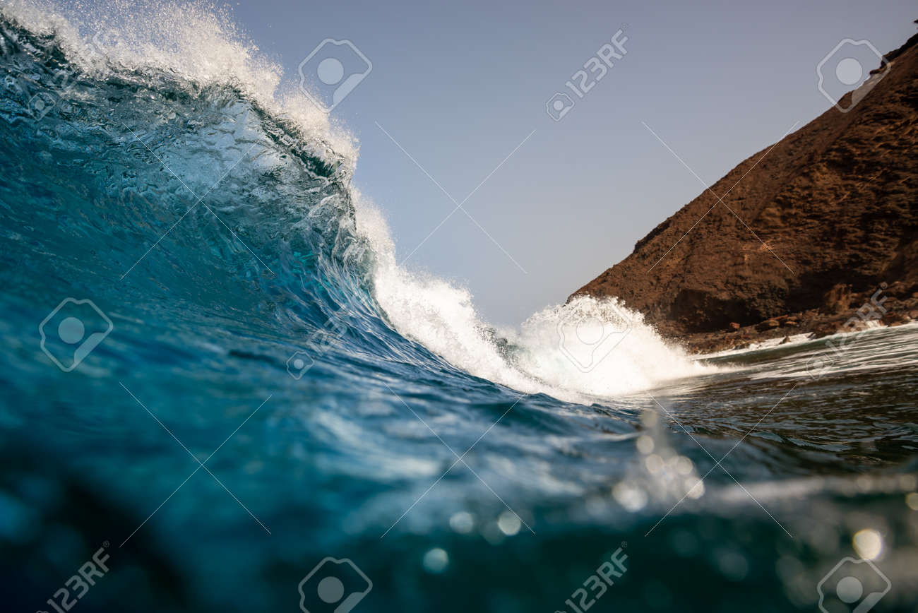 breaking wave with the tube and blue water with the clouds at the background - 142686354