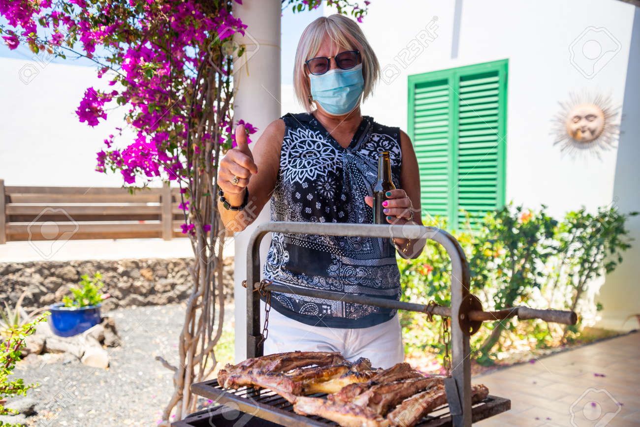 elderly lady cooking on a barbecue with face mask - 147309943