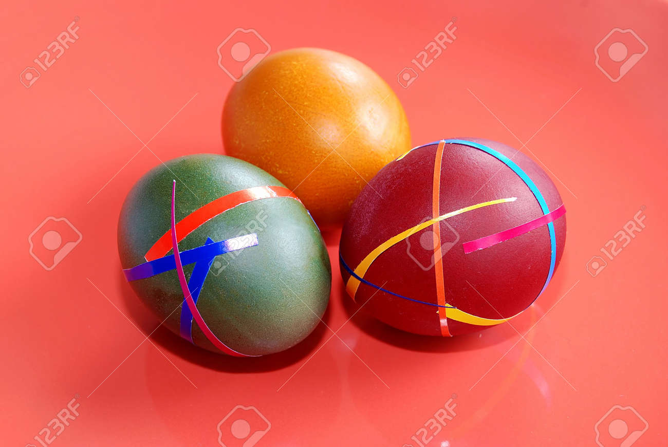 three colored ester eggs isolated over red Stock Photo - 3779932