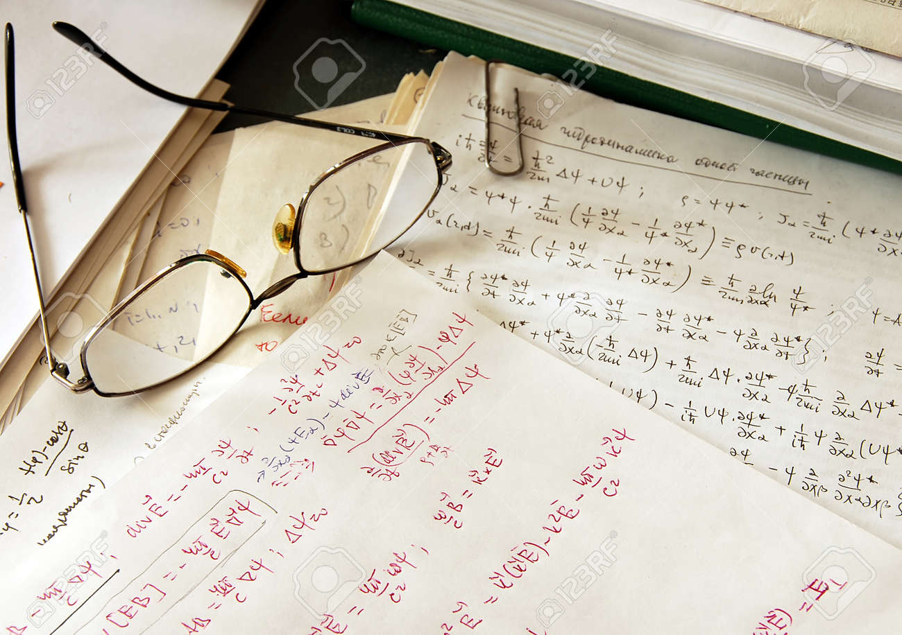glasses over physics formulas and calculations written on paper - 10333751