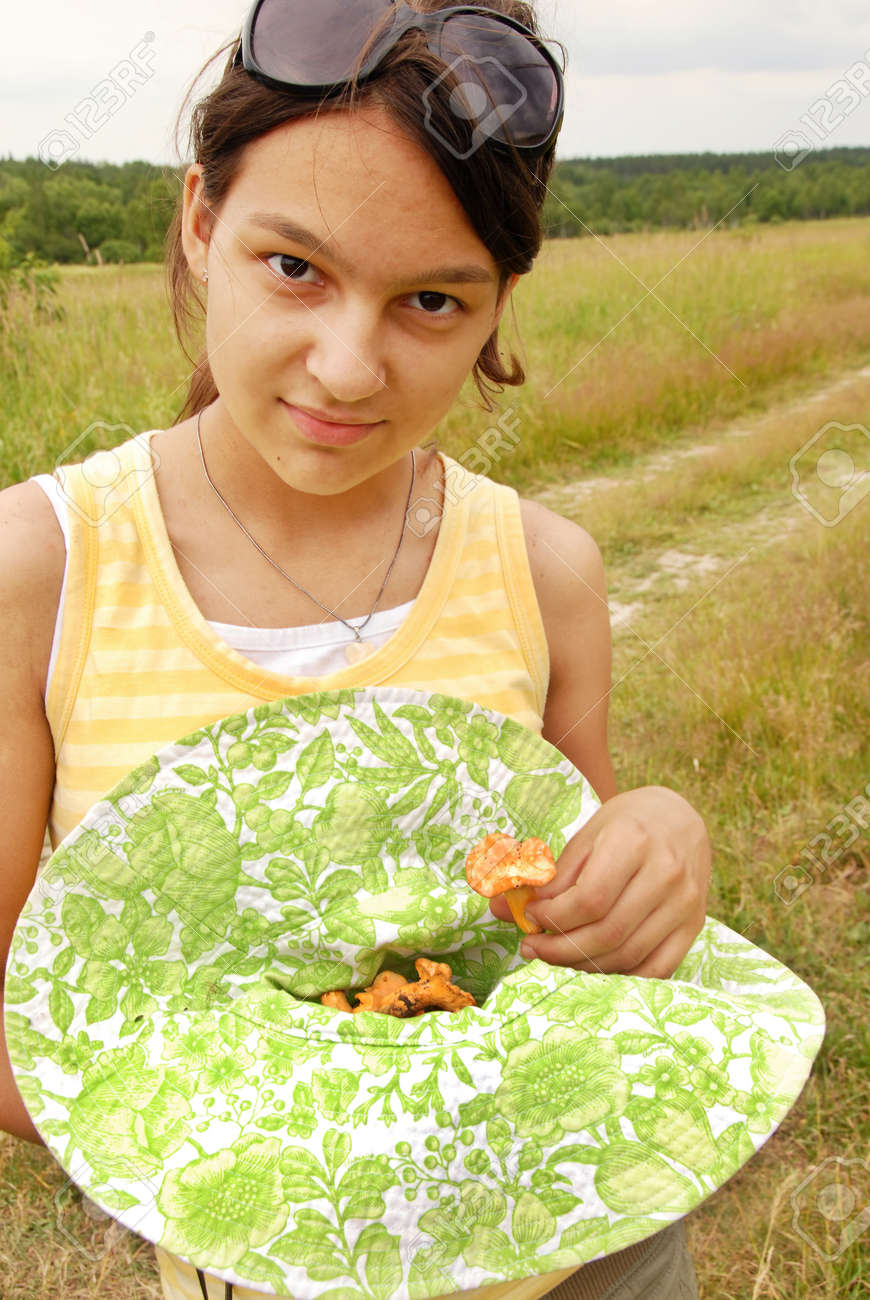 portrait of young smiling teenage caucasian girl outdoors with chanterelle mushrooms Stock Photo - 10349341