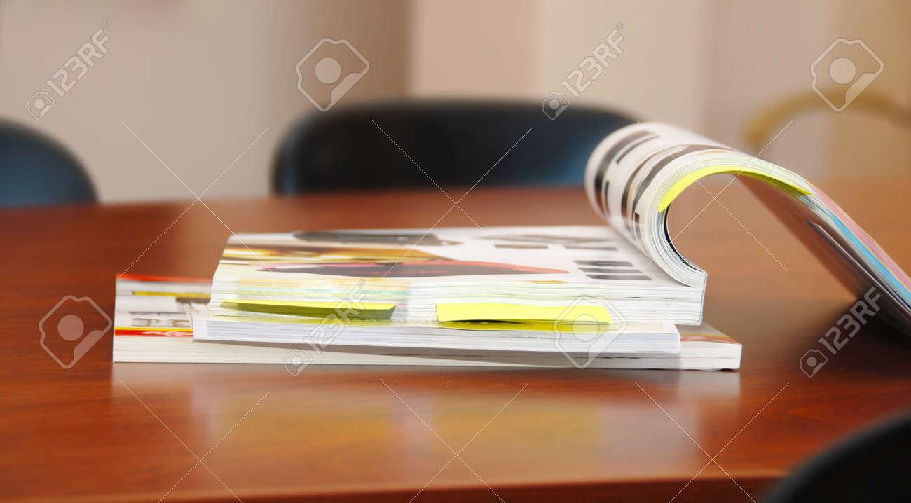 opened magazines on brown business desk indoor - 10411083