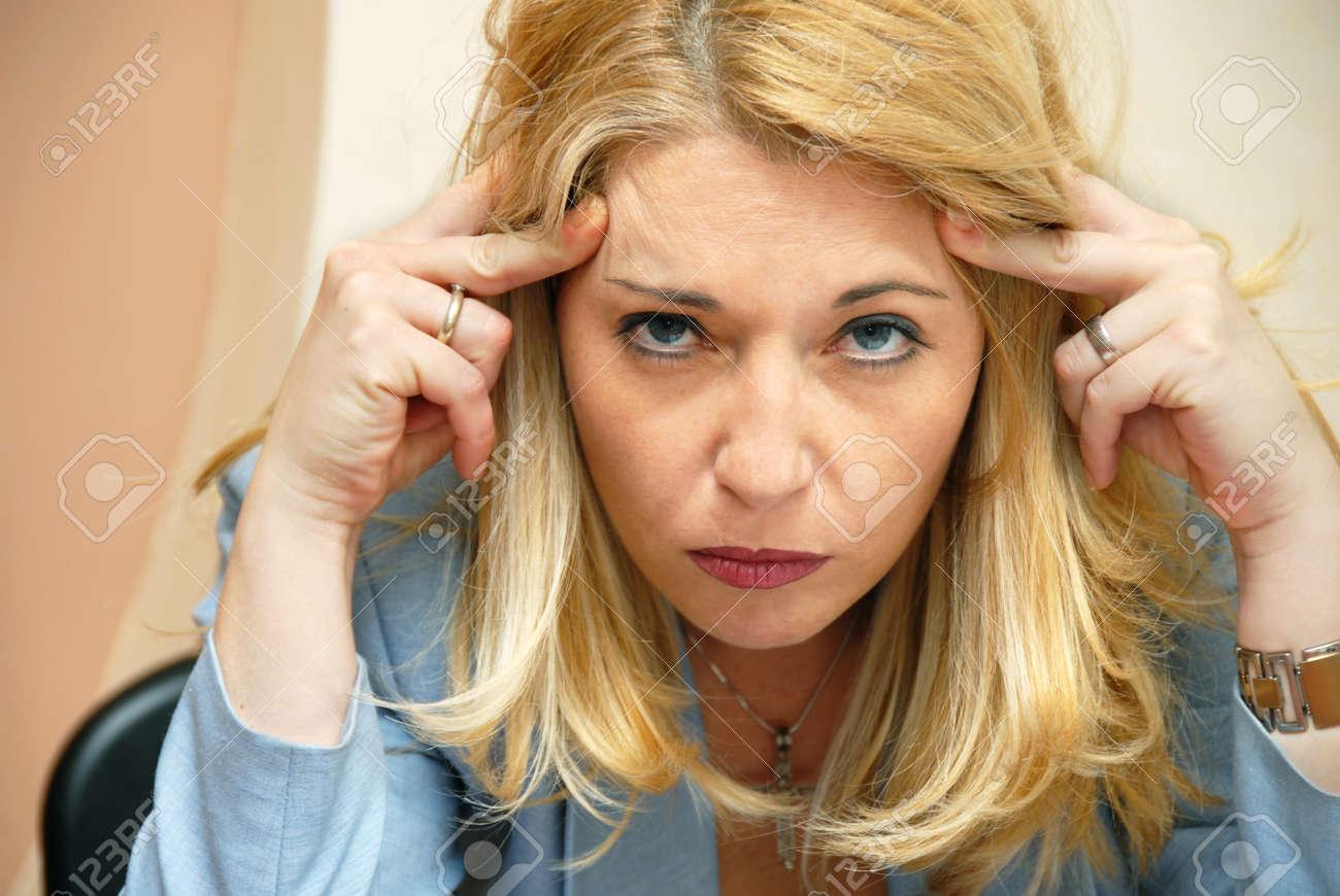 blond businesswoman suffering from headache indoor portrait - 10427553