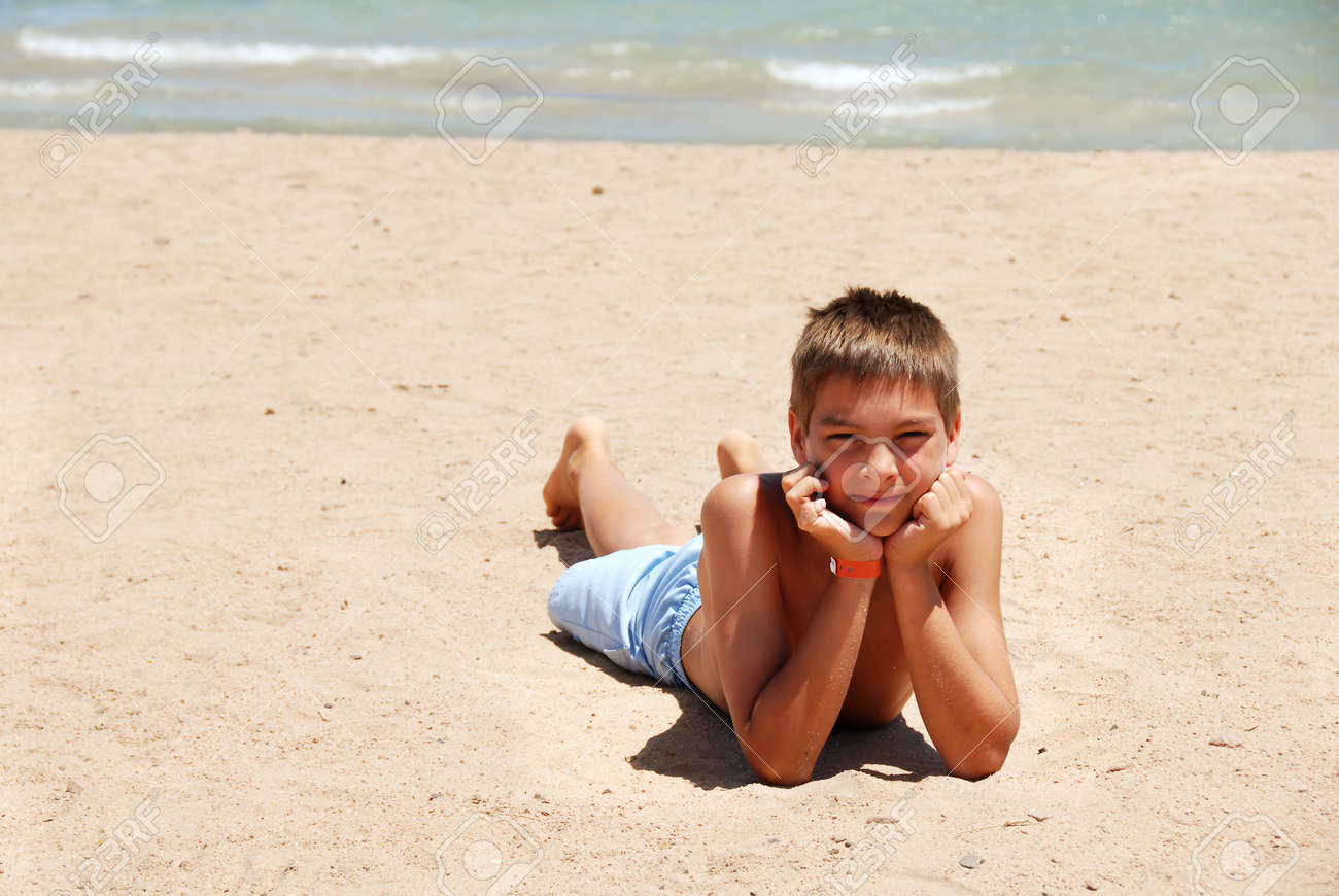 caucasian boy lying on the sand beach in Egypt Stock Photo - 10432390