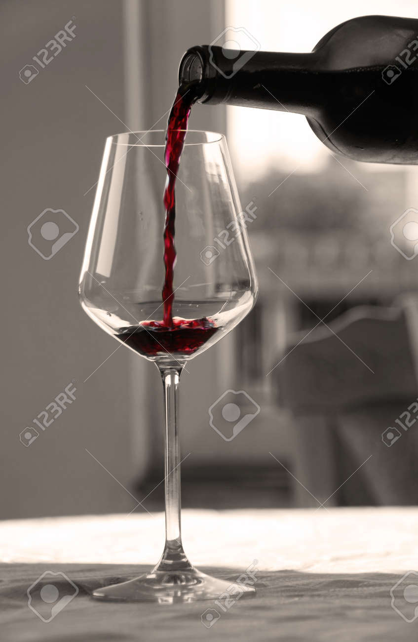 pouring red wine from bottle into wineglass in black and white - 10528058