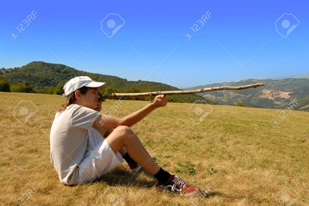 boy sitting on mountain meadow aiming with a stick as a gun Stock Photo - 10728362