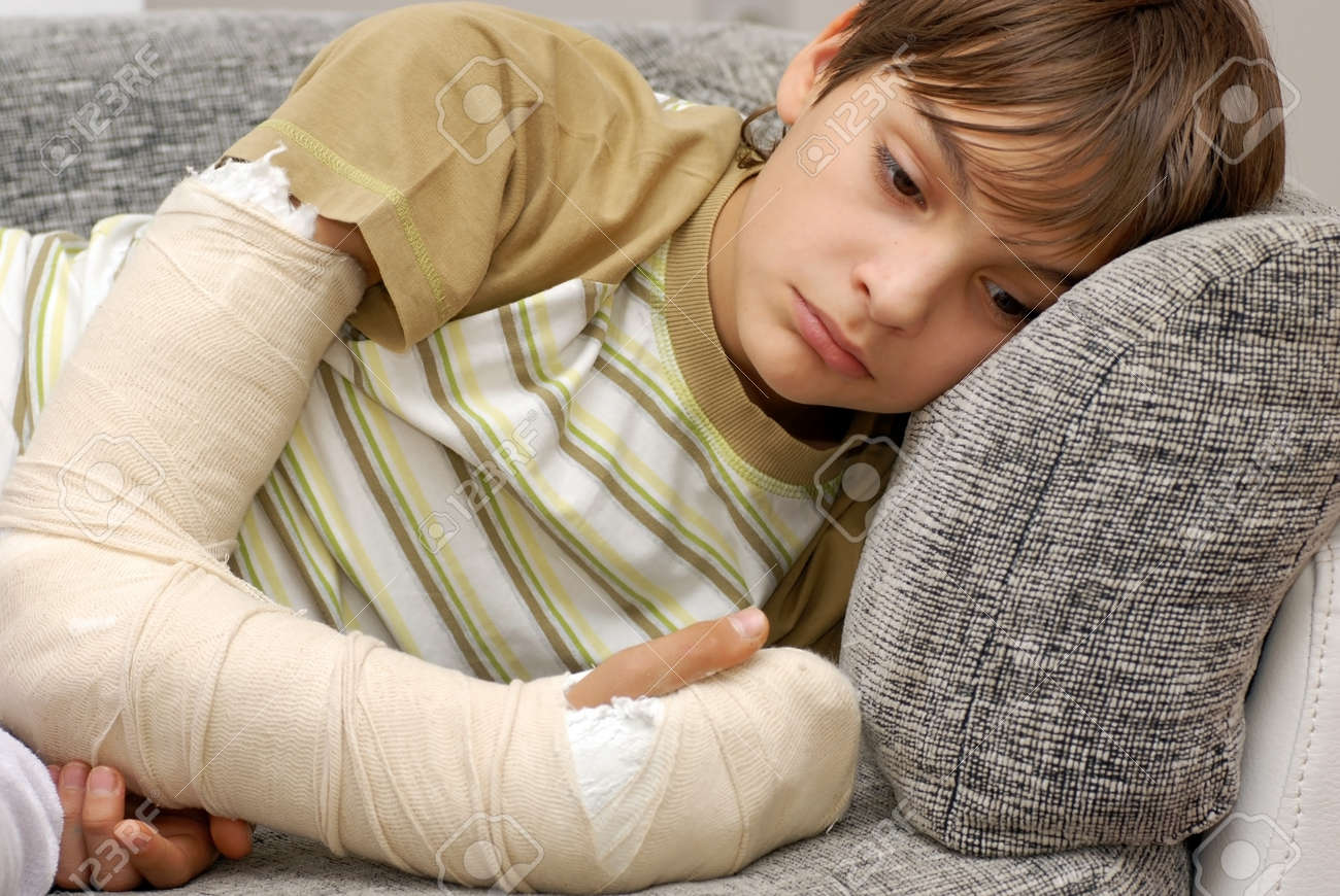 sad teenage caucasian boy with broken arm bone - 12026978