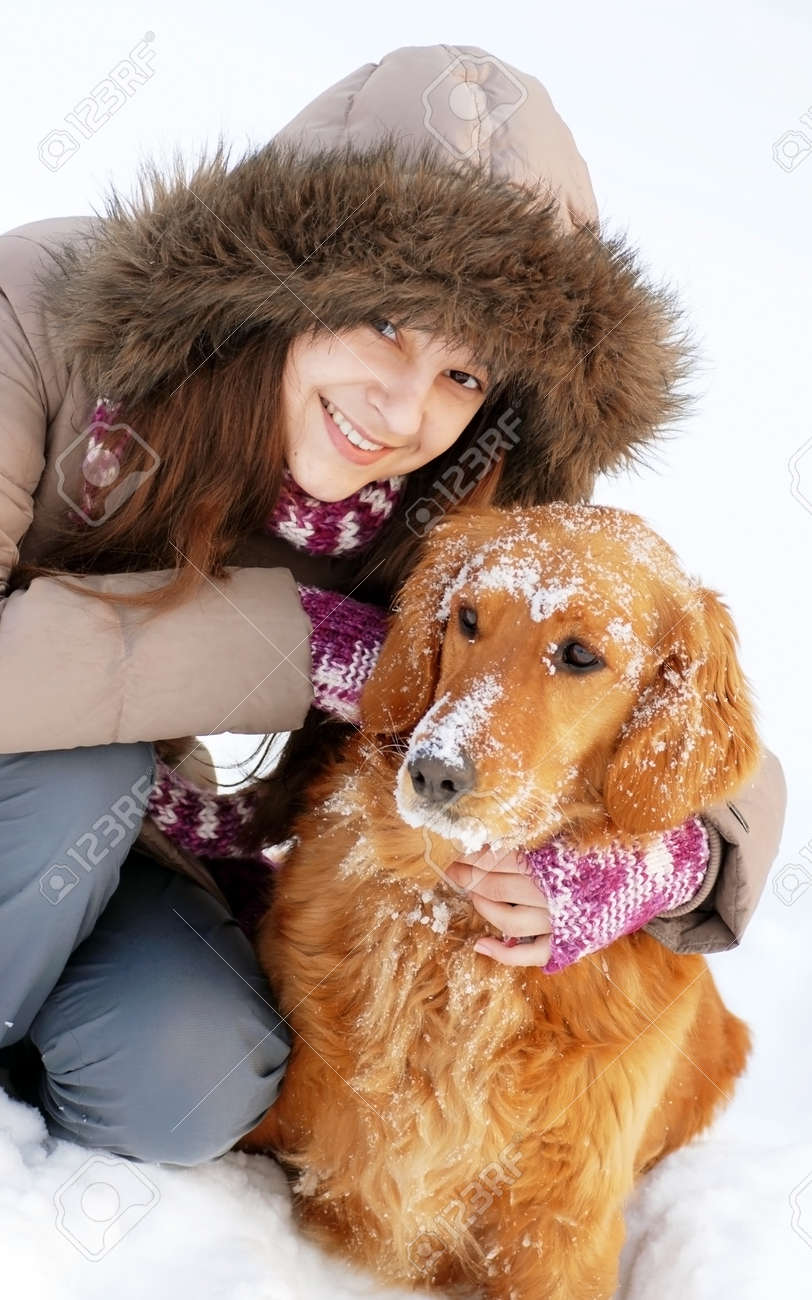 smiling teenager caucasian girl in hood hugging her dog outdoors at snow - 13013680