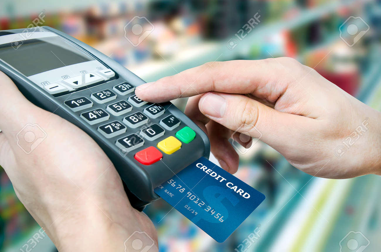 Hand With Credit Card Swipe Through Terminal For Sale In Supermarket ...