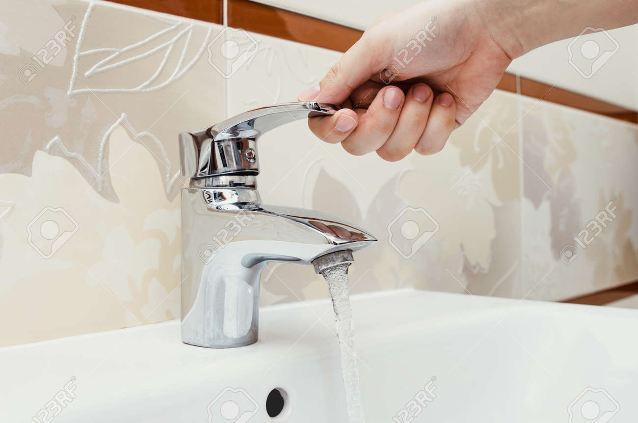 Man Unscrew The Faucet In The Bathroom Utilities Water Bill Stock - Bathroom utilities