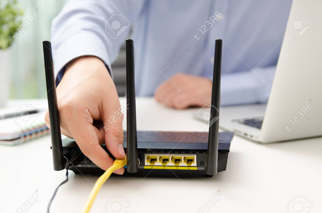 Man Plugs Ethernet Cable Into Router. Router Wireless Wire Broadband ...