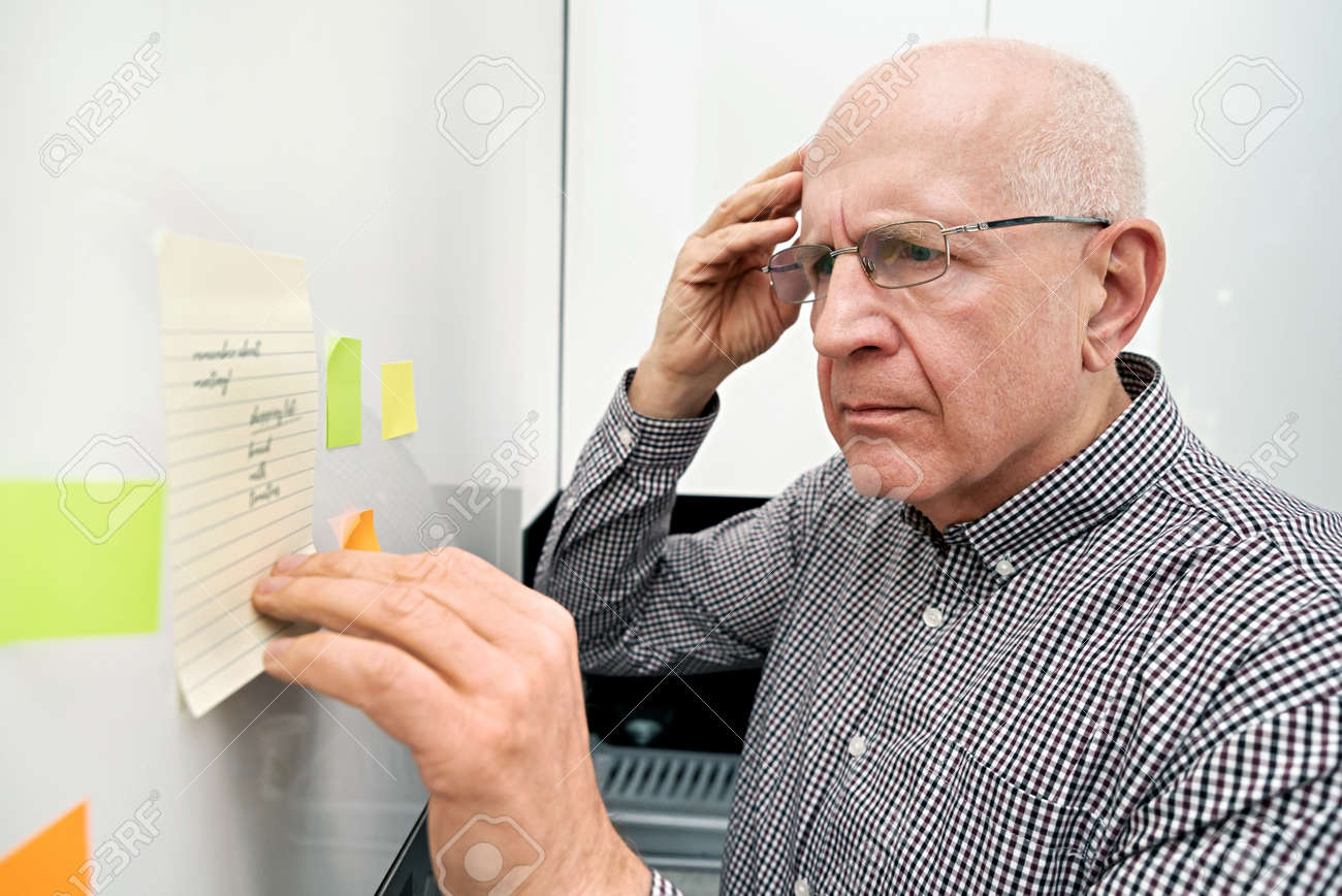 Elderly man looking at notes. Forgetful senior with dementia, memory problem, health concept - 121947801