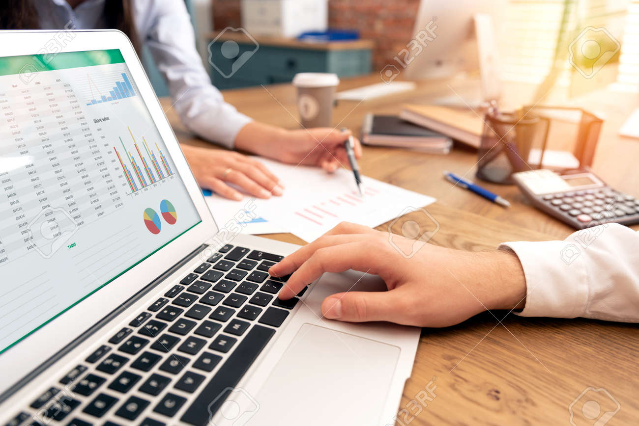 Investors work in the office. Financial advisor with laptop and graph on the screen. Woman pointing on statement - 135093623