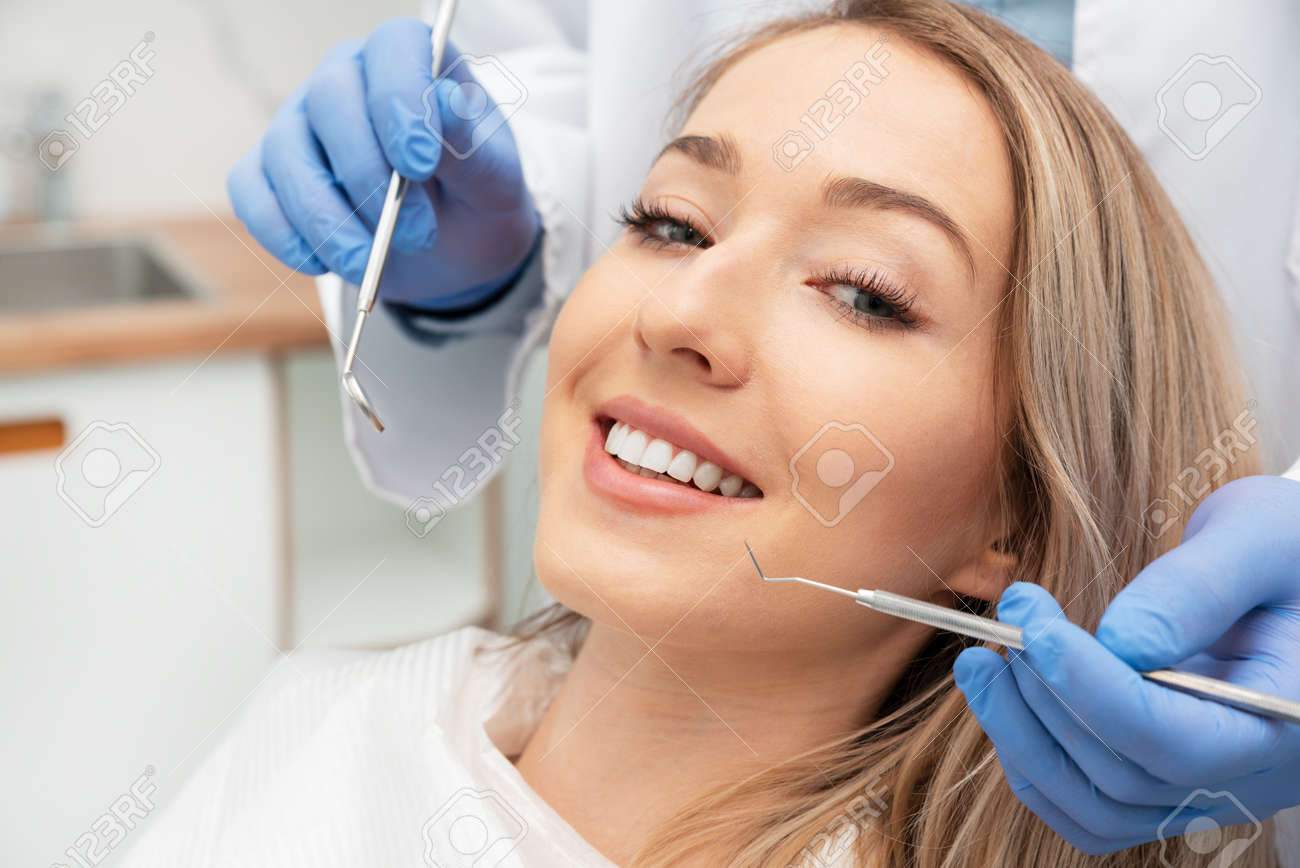 Woman having teeth examined at dentists. Teeth whitening, dental care concept - 147982223