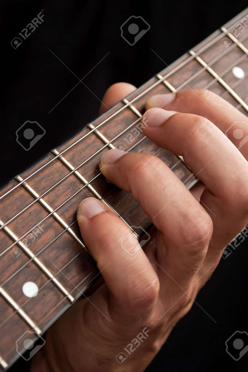 Hand On Guitar Fretboard Close Up Stock Photo