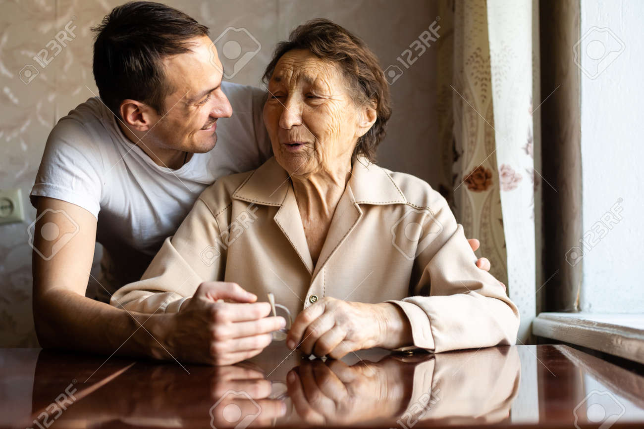 a very old woman and an adult grandson - 164678306