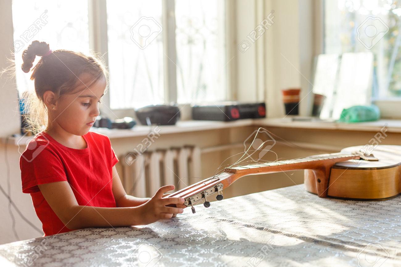 little girl holding a broken guitar, guitar repair - 162442639