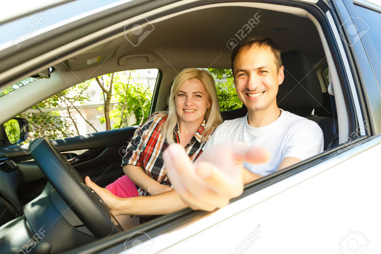 Happy young man and woman in a car enjoying a road trip on a summer day. - 165061372