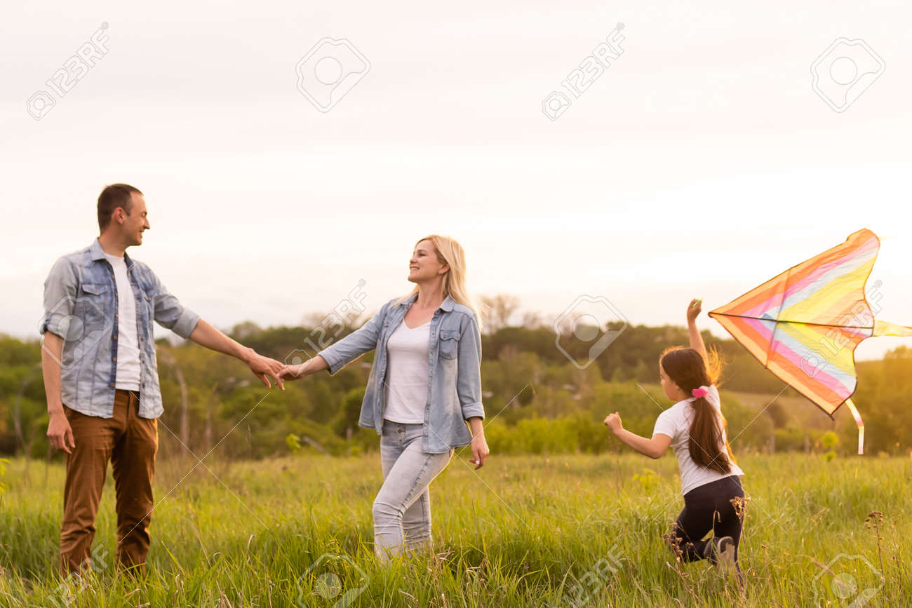 Happy family in the park evening light. The lights of a sun. Mom, dad and baby happy walk at sunset. The concept of a happy family - 169783851