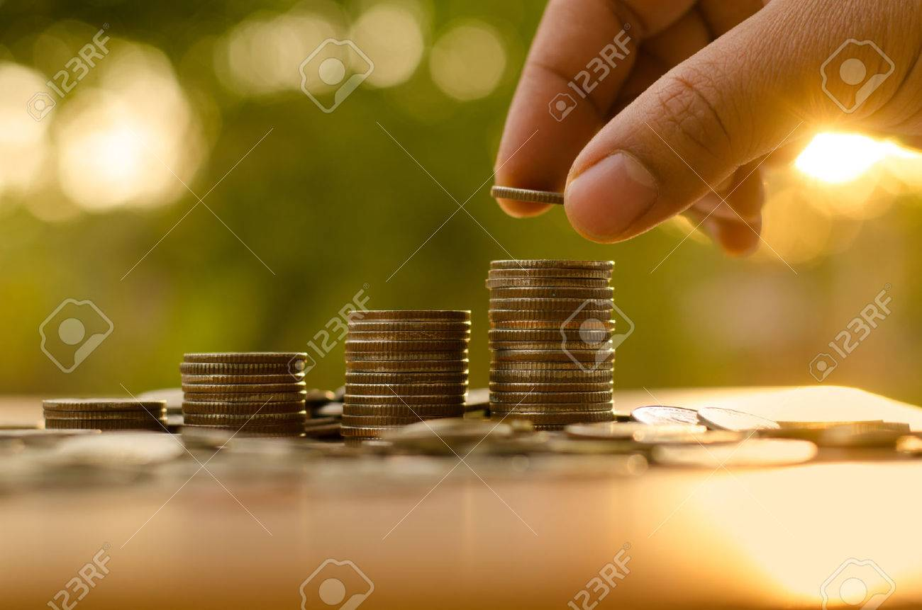 Male hand putting coin stack growing graph with sunlight - 36333069