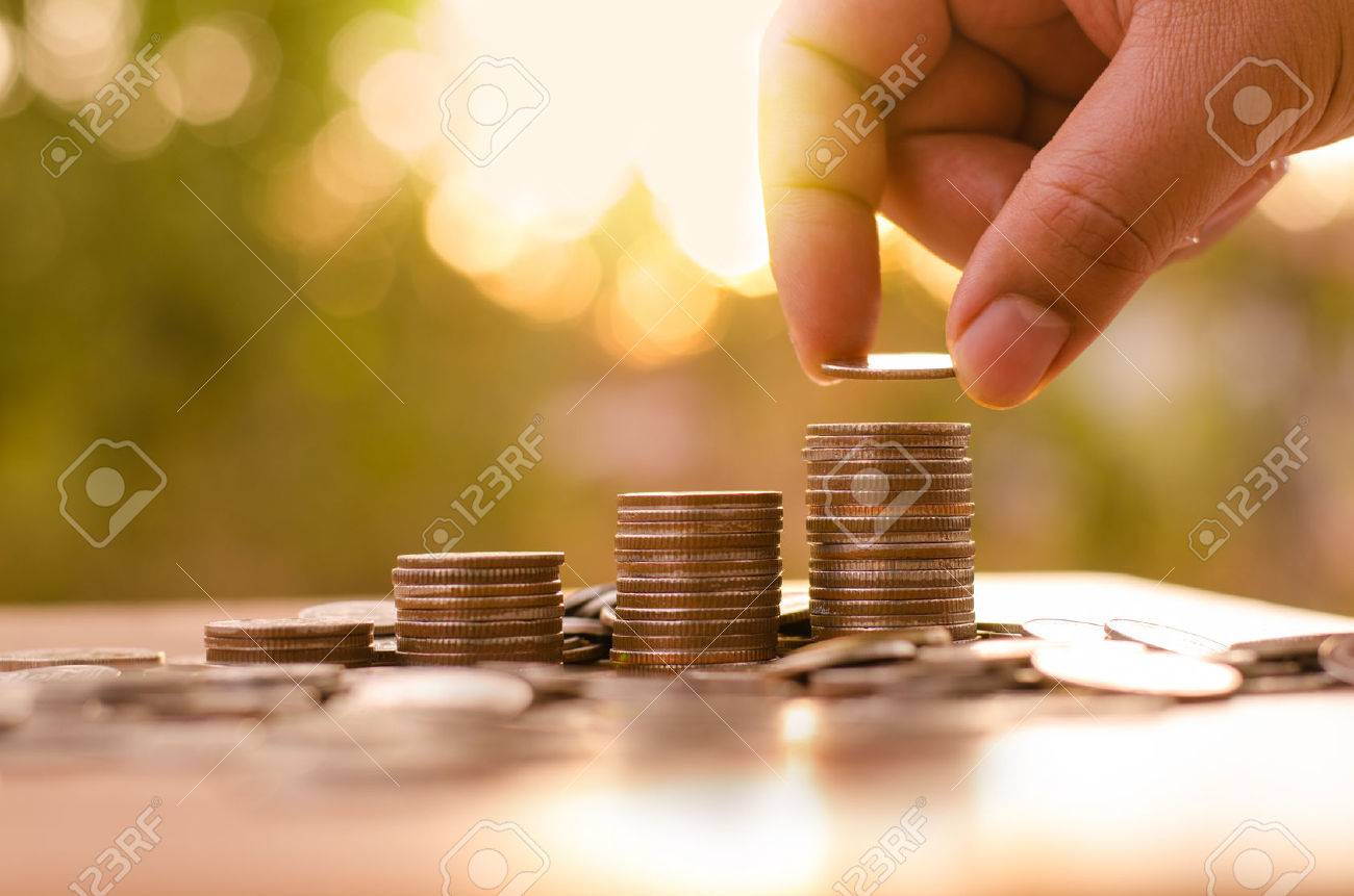 Male hand putting coin stack growing graph with sunlight - 36333071