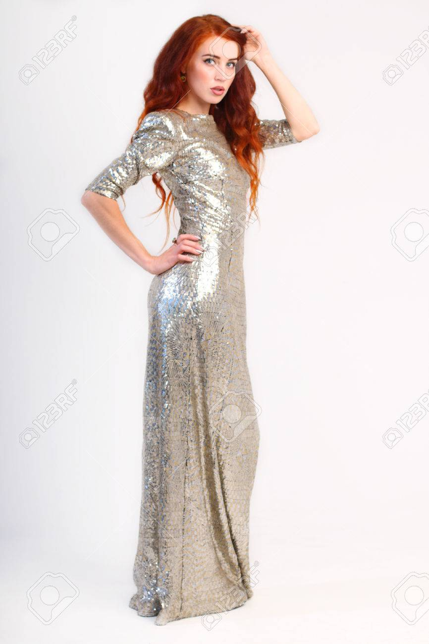 Beautiful Girl With Red Hair And Shiny Silver Dress In Studio