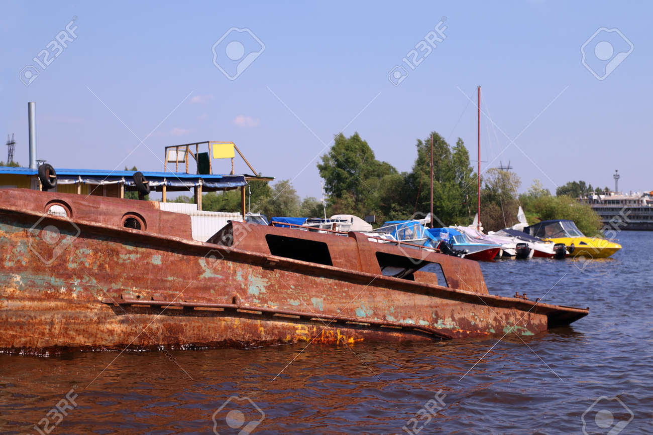 Old abandoned rusty boat in river and new motor boats on summer old abandoned rusty boat in river and new motor boats on summer day stock photo publicscrutiny Image collections