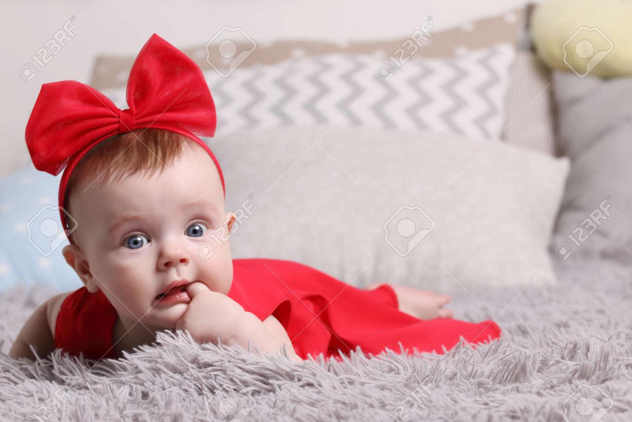 6ebf708e6 Bebé Serio En Vestido Rojo Y Arco Con La Mano En La Boca Está En La ...