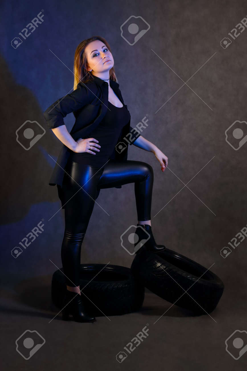 Women with make-up in black poses on tires in studio with blue