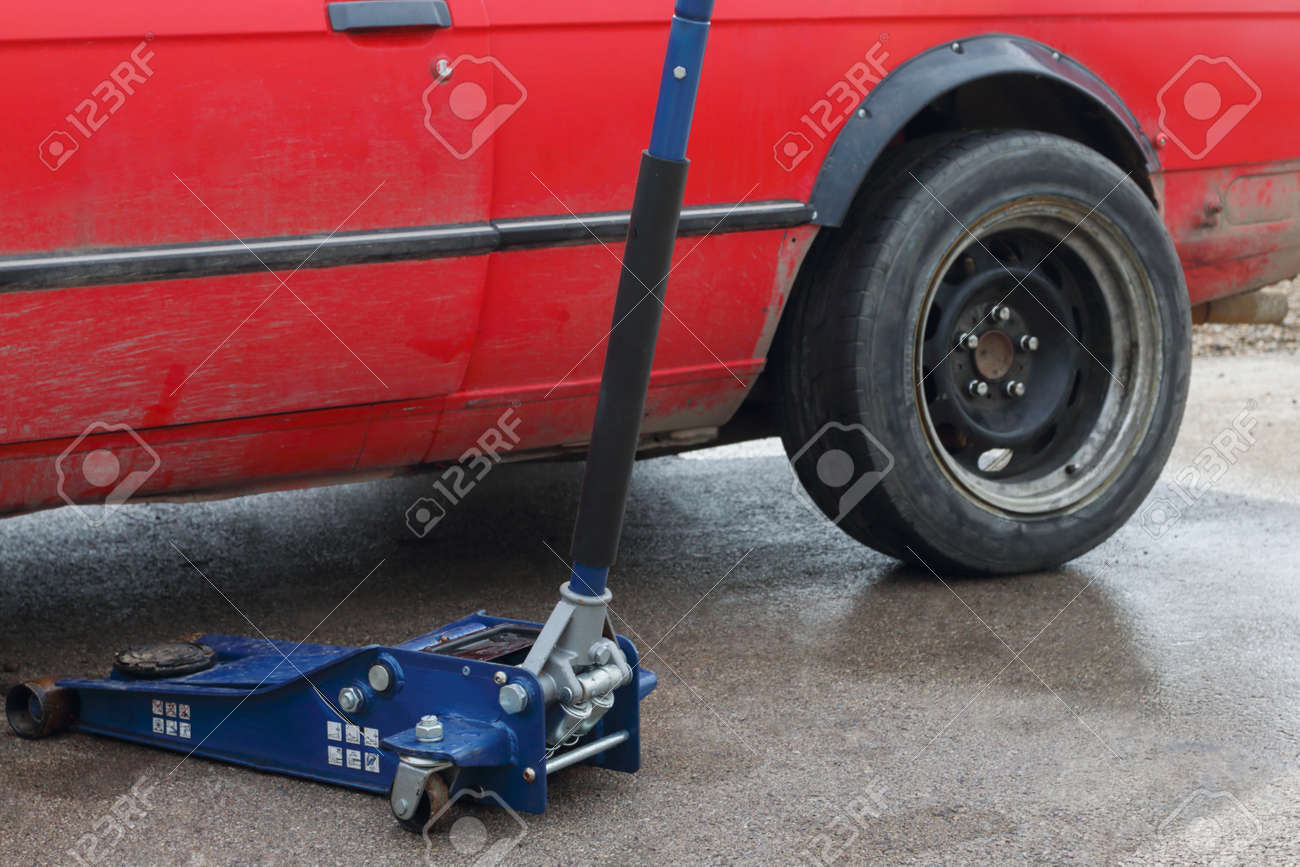 Part of car and tool for car repairing - levelling jack on asphalt