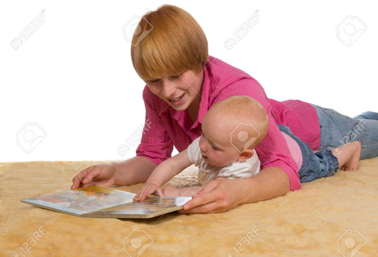 Mother lying on the floor with her arm protectively around her cute young baby looking at a book together Stock Photo - 14421663