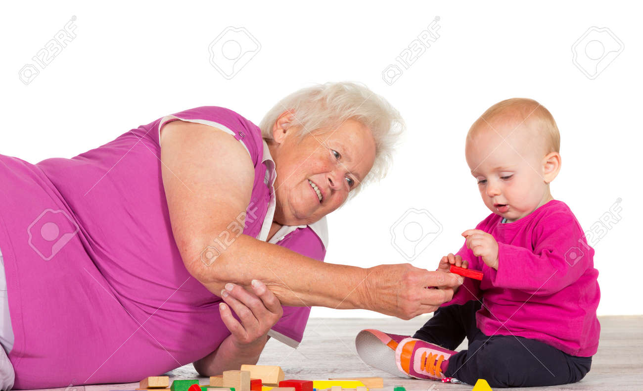 elderly grandmother lying on the floor babysitting her small elderly grandmother lying on the floor babysitting her small grandchild as the two play contentedly together