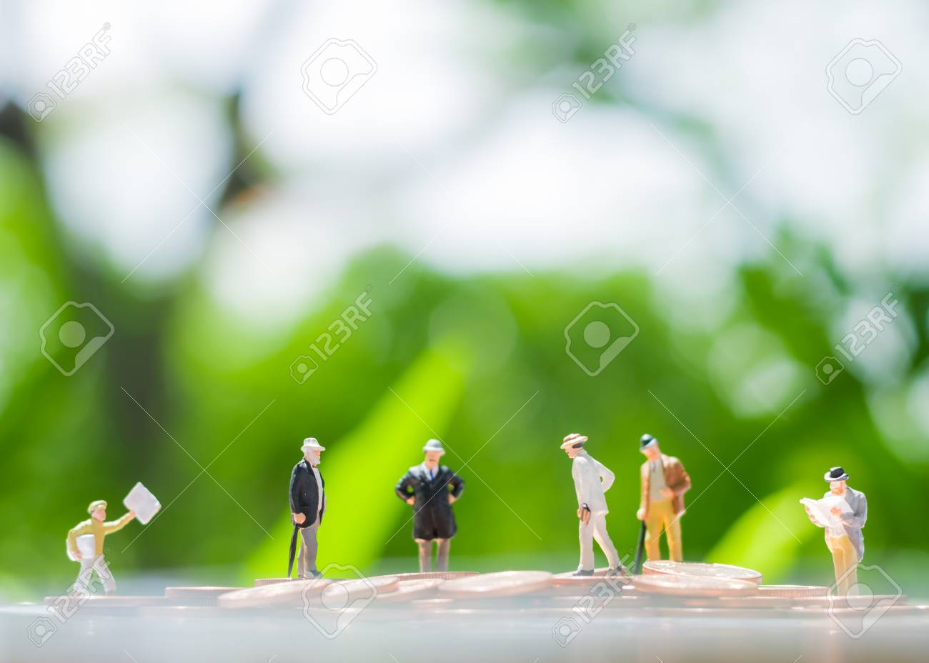 Tiny Miniature Models Of Businessman Are Standing On A Pile Of