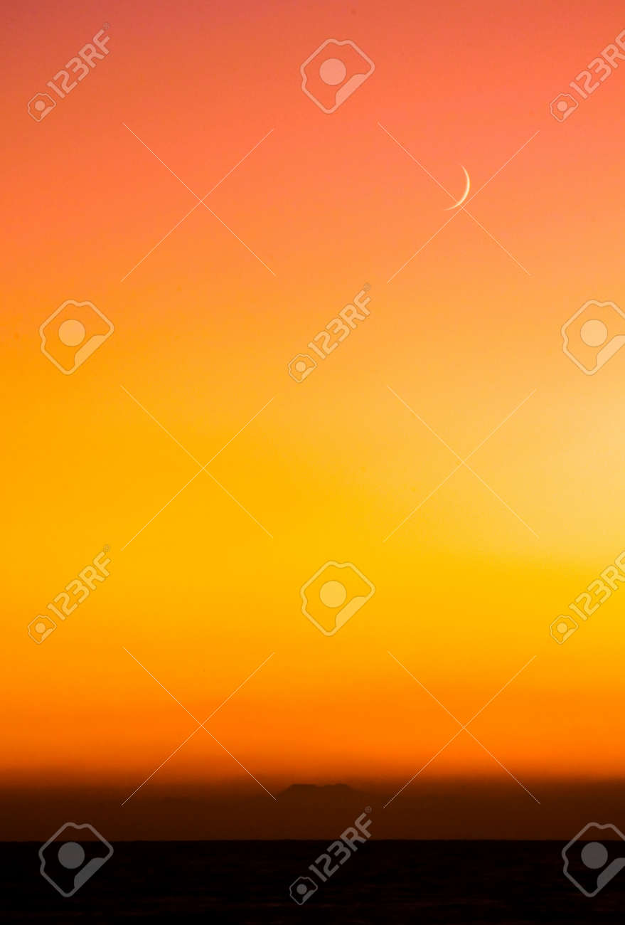 Sliver Moon appearing above a distant island at sunset. Stock Photo - 11505375