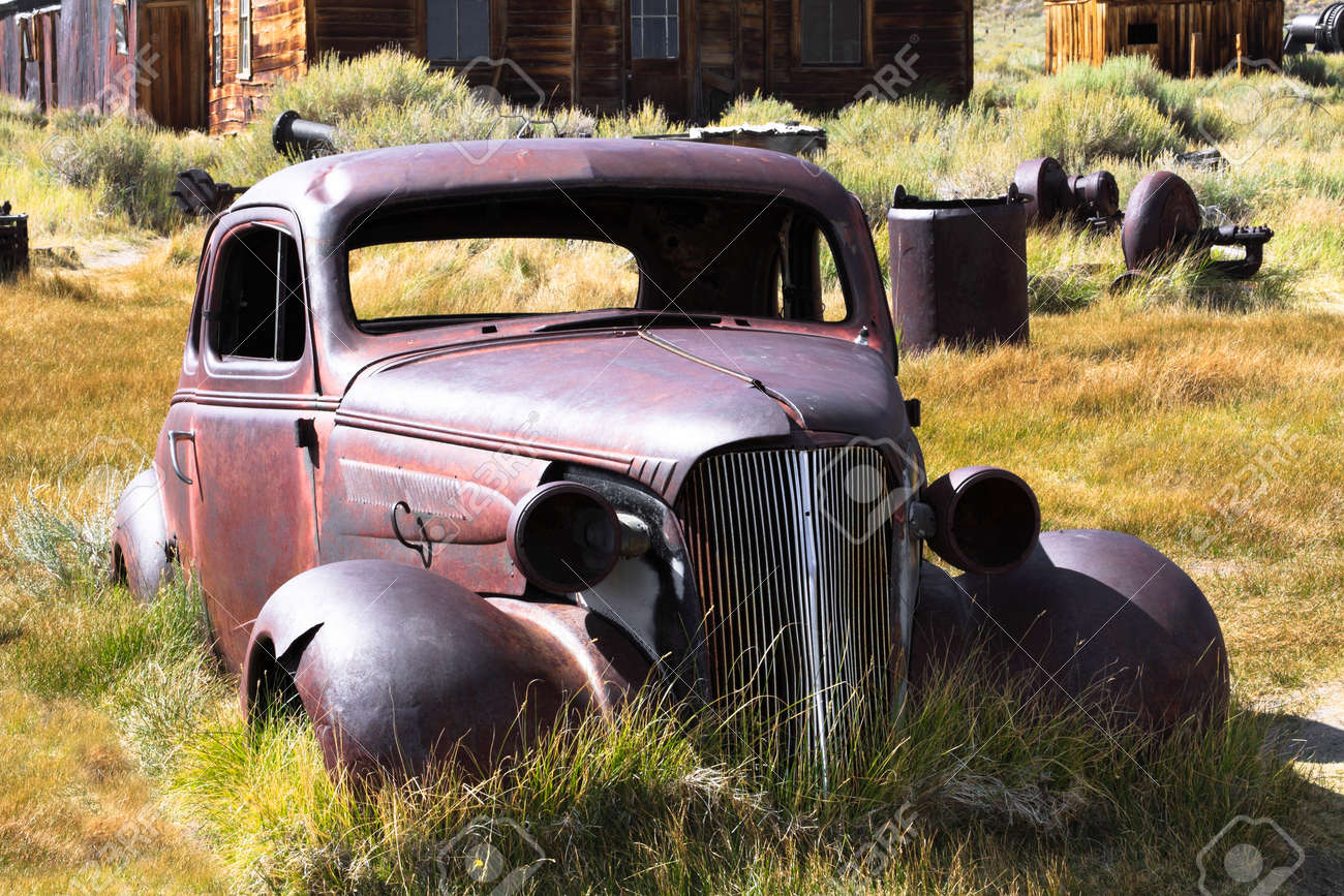 1937 Chevy without wheels abandoned in the desert with house as a background. Stock Photo - 11508047