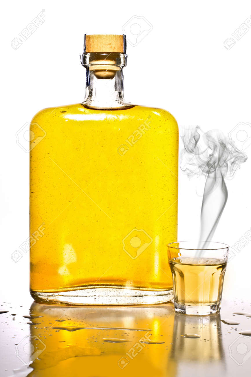Unlabeled bottle of tequila with a filled shot glass with smoke. Stock Photo - 12539057