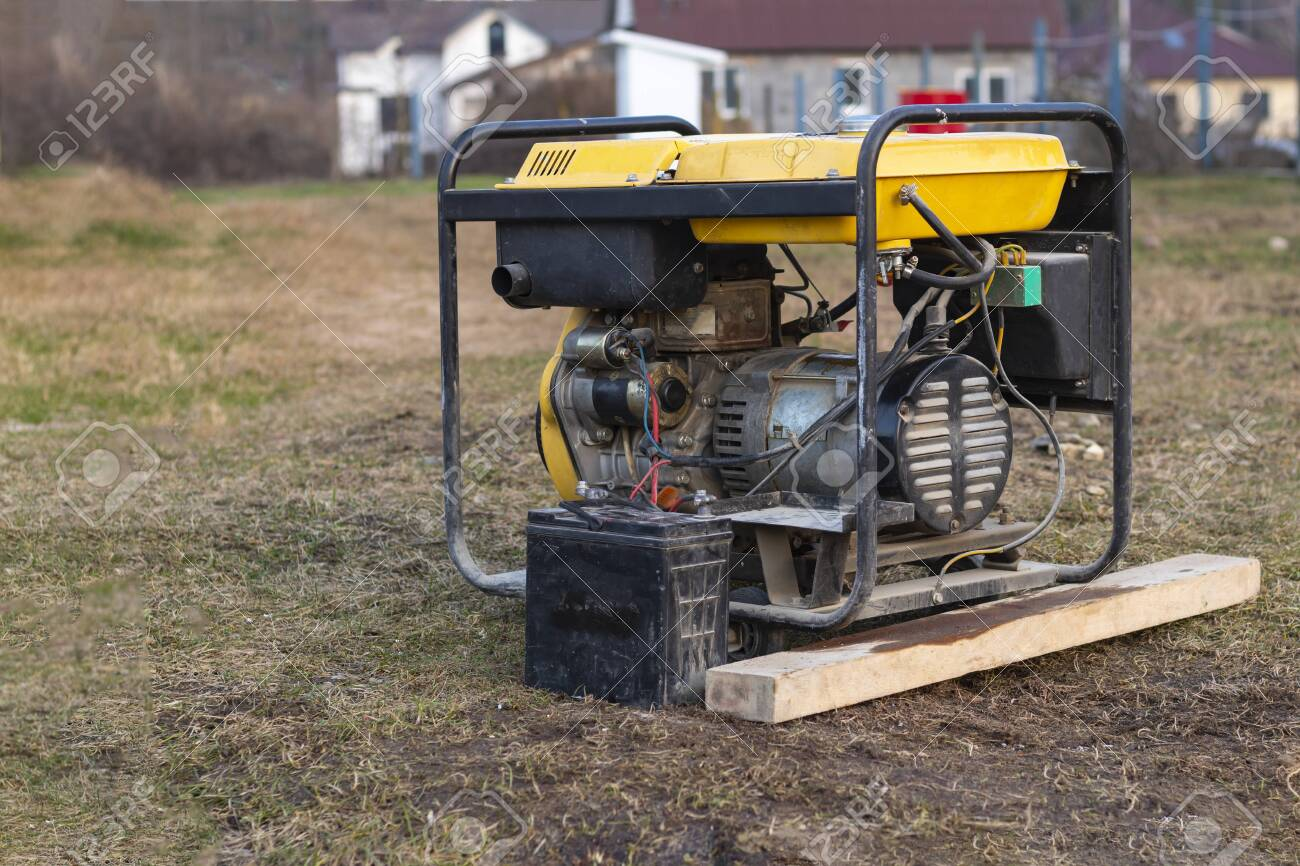 close-up. Street lighting. A gasoline-powered generator that produces current. A car battery is connected for charging. Backup or emergency power source. The generator is not new. - 137975126