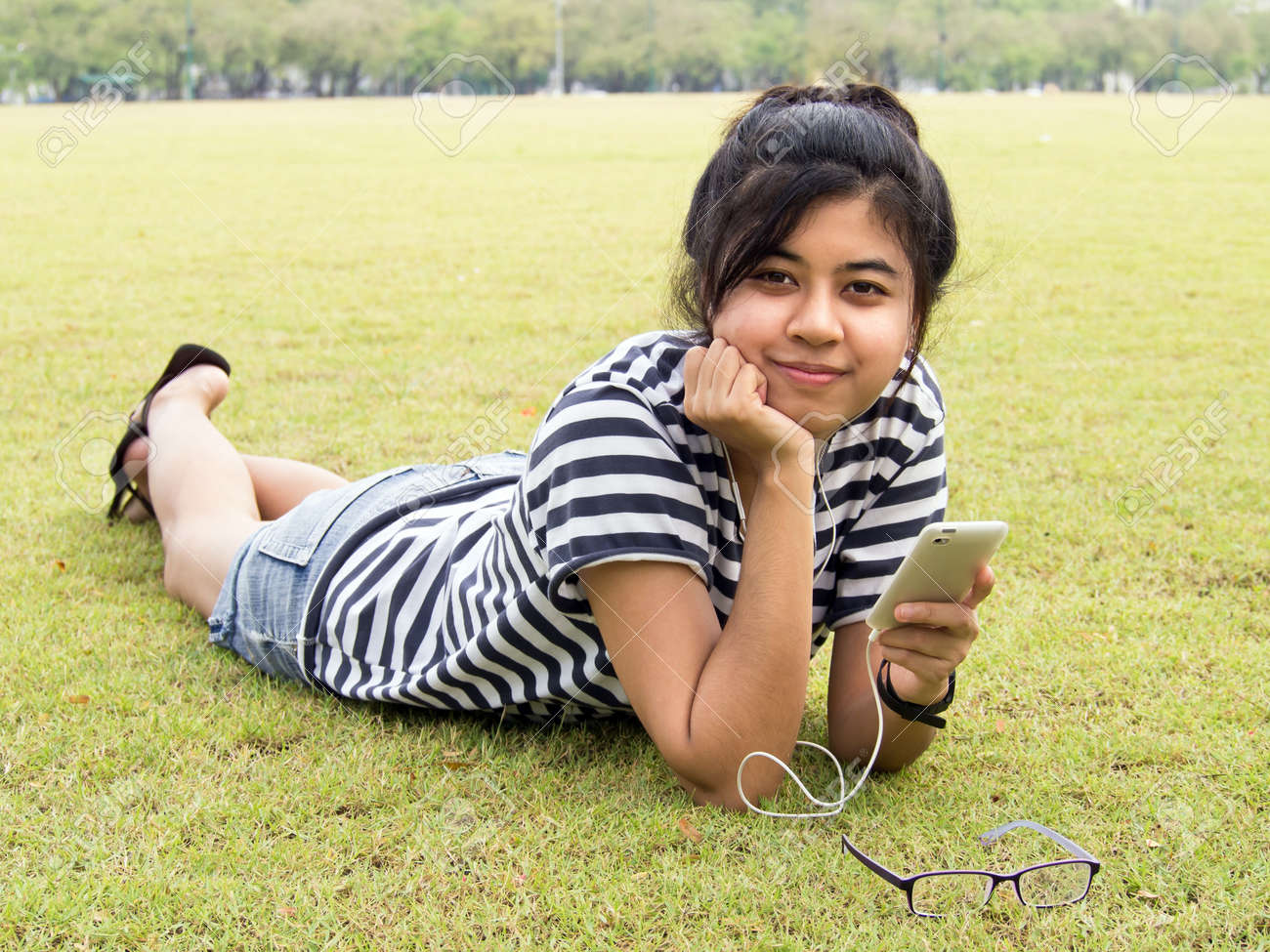 A young girl lie down on grass with headphones outdoors. Listening music Stock Photo - 13053246