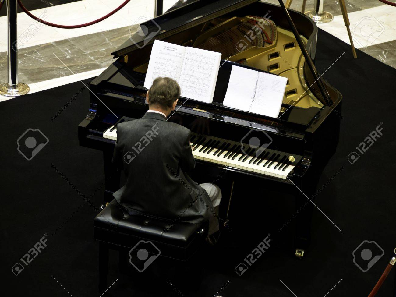 senior man playing on a grand piano, from back view Stock Photo - 15460995