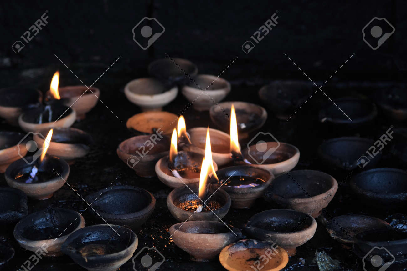Photo of offering lit candles in dark buddhist sacrificial altar