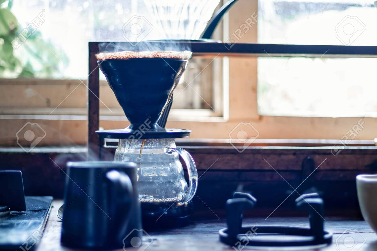 Vapor coming out of a coffee cup and brewing fresh coffee in the background - 142145072