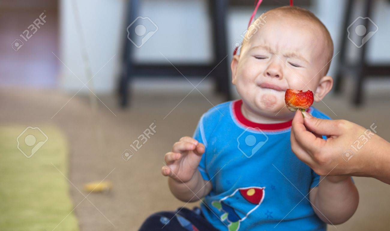 A shot of a young baby boy just taking a bite of a sour strawberry. Banque d'images - 5737701