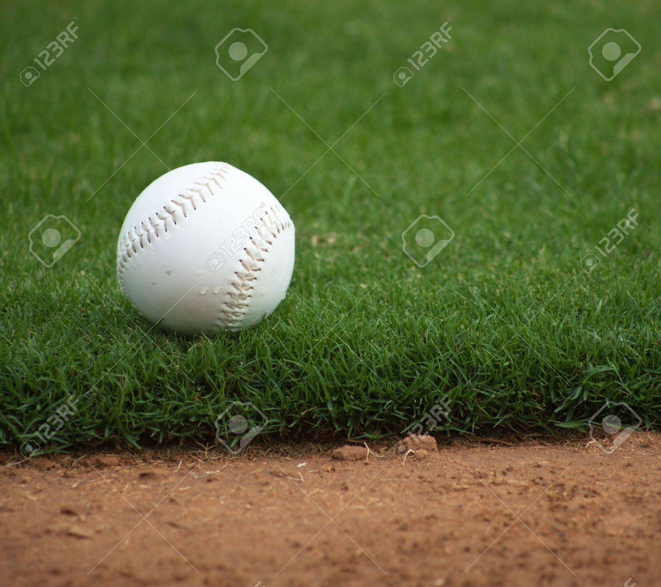 A close up of a softball sitting just off the infield dirt. Banque d'images - 5790795