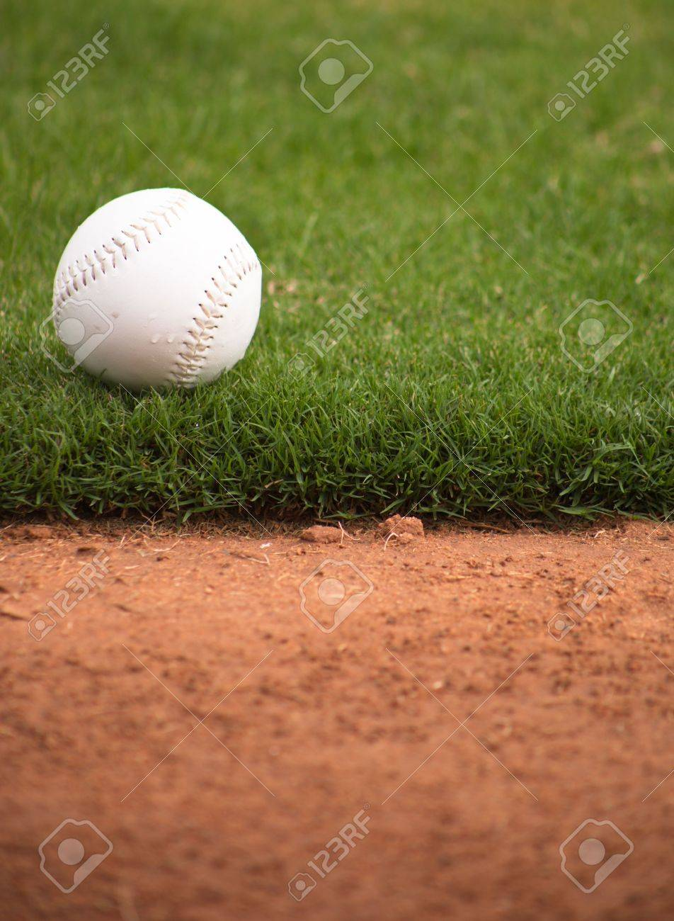 A close up of a softball sitting just off the infield dirt. Banque d'images - 5790797