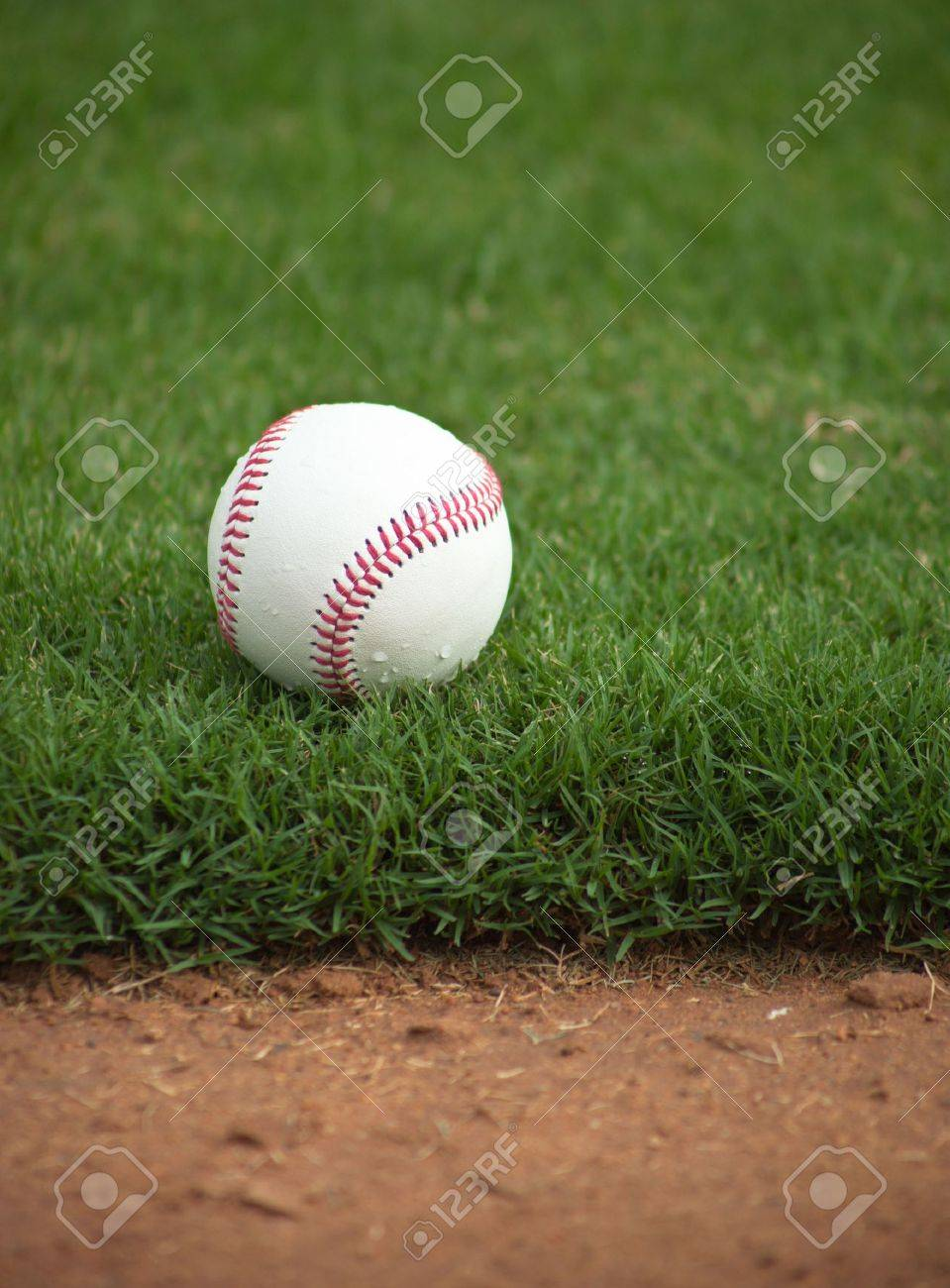 A close up of a baseball sitting just off the infield dirt. Banque d'images - 5790798