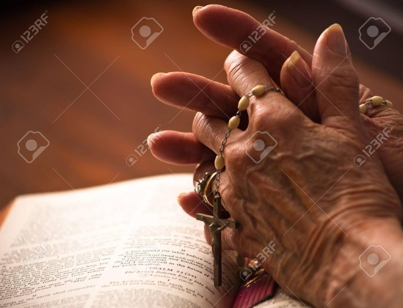 Un gros plan d'une main de womans supérieurs sur la bible avec un rosaire. Banque d'images - 6328190