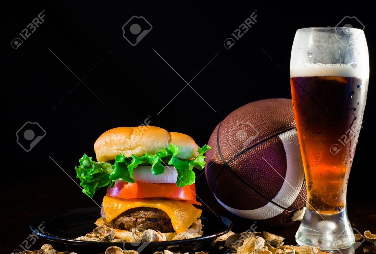 A close up of a big hamburger surrounded with peanuts, beer and a football. Banque d'images - 8750251