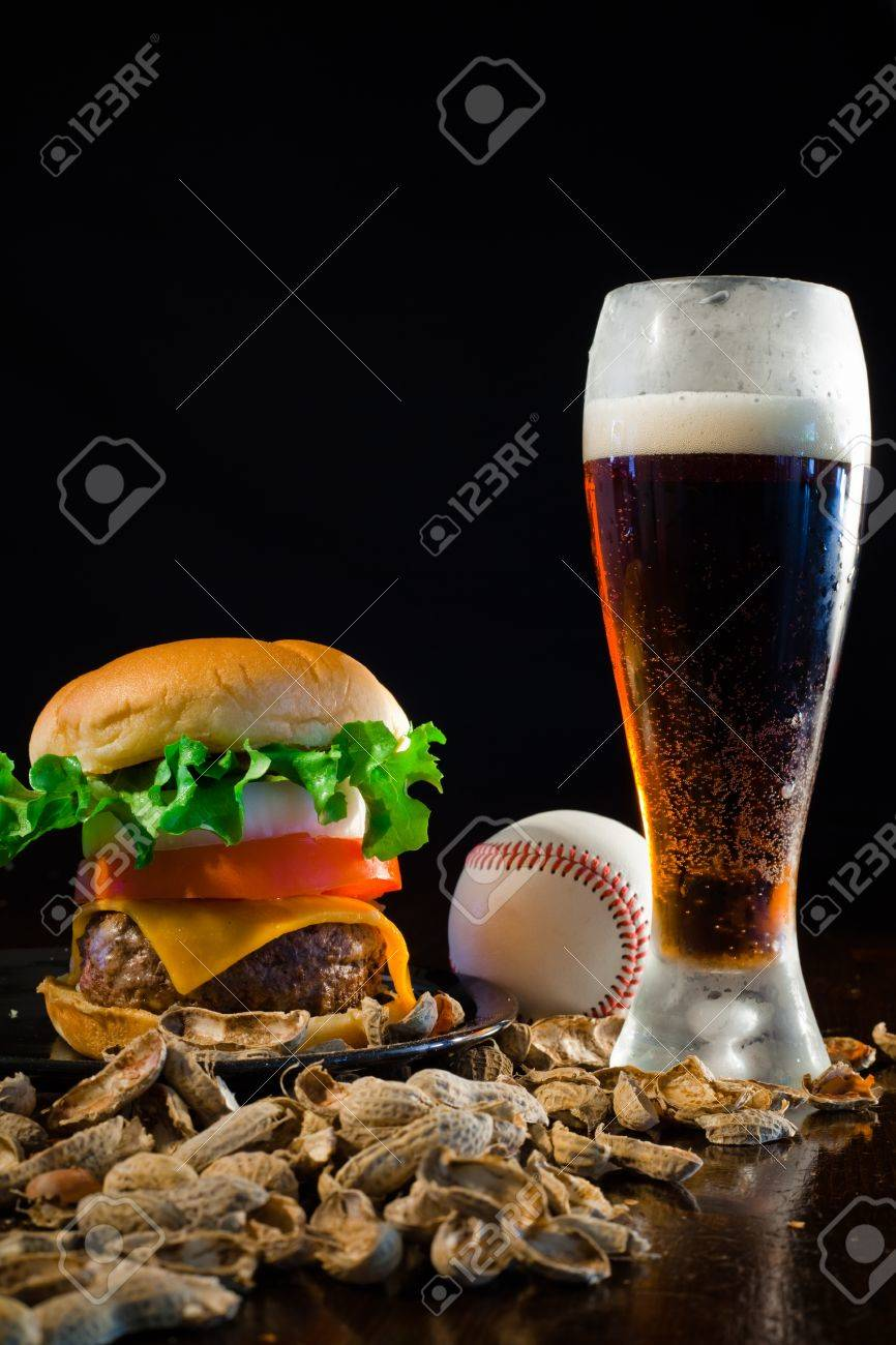 A close up of a big hamburger surrounded with peanuts, beer and a baseball ball. Banque d'images - 8750240