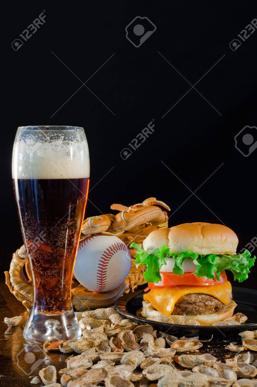 A close up of a big hamburger surrounded with peanuts, beer and a baseball glove and ball. Banque d'images - 8750244